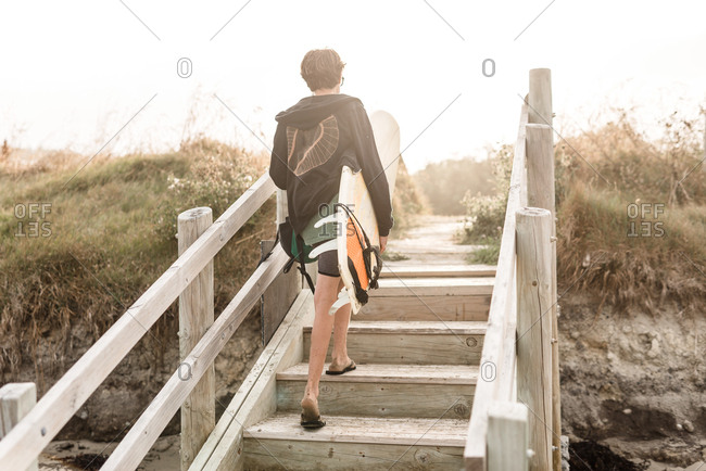 Rear view of teen walking up steps on beach with surfboard
