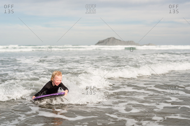 Young boy riding a small wave on a boogie board in the ocean