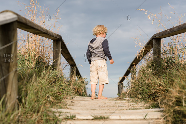 Young boy looking away at top of steps at beach