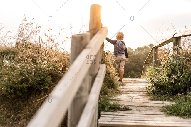 Young boy walking on wooden path at beach