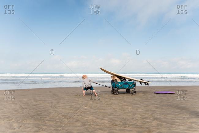 Little boy pulling wagon with surfboard on beach