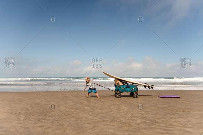 Young boy pulling wagon with surfboard on beach