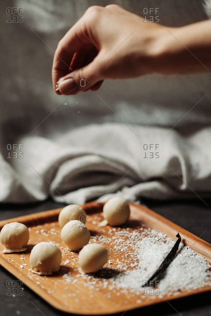Woman sprinkling coconut over vanilla pralines
