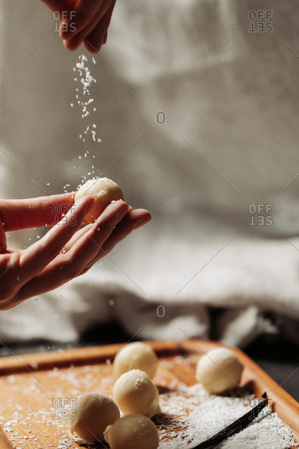 Baker sprinkling coconut over vanilla pralines