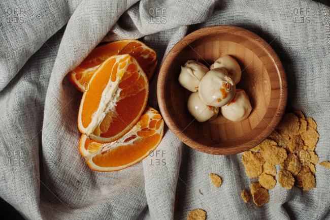 Overhead view of orange and white chocolate pralines  in a wooden bowl