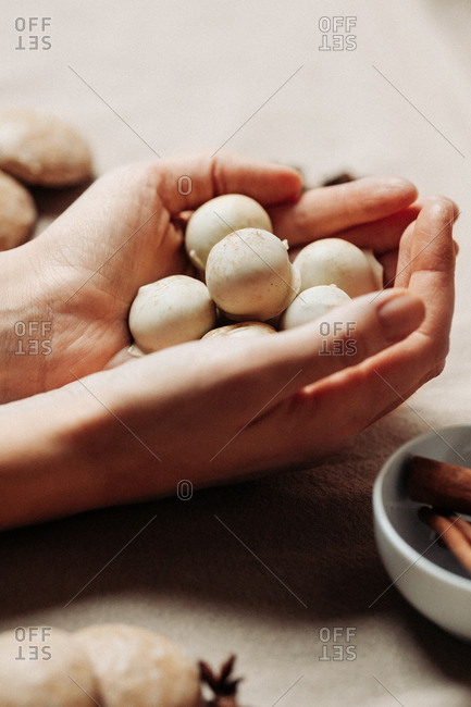 Woman holding pralines by cookies and cinnamon and star anise
