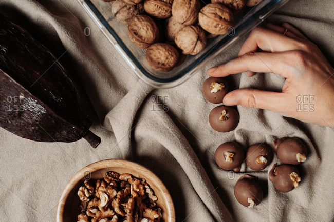 Woman touching a milk chocolate walnut pralines