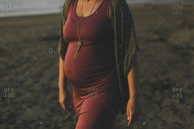 Pregnant woman walking on a beach at sunset