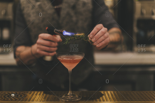 Bartender preparing cocktail with torched rosemary