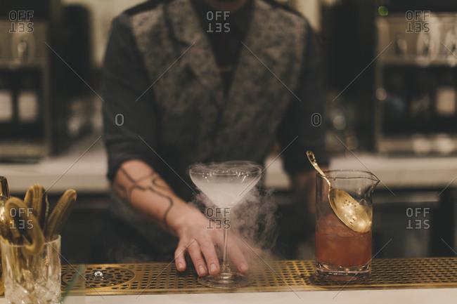 Bartender preparing misty cocktail - Offset