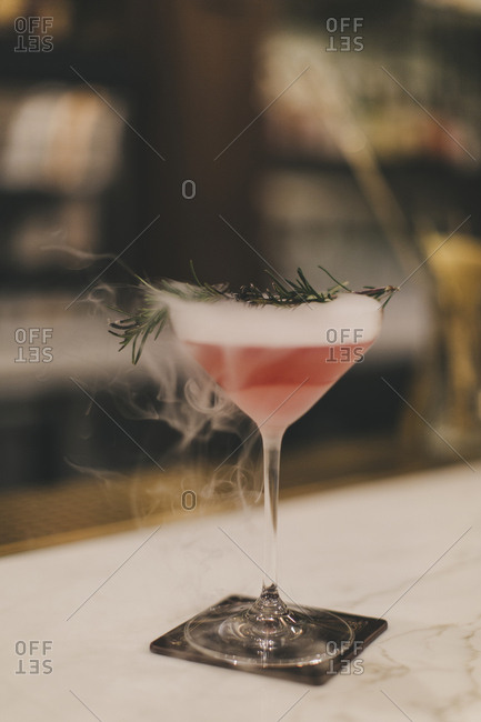 Misty cocktail with rosemary garnish