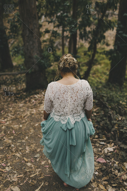 Rear view of bride walking in forest