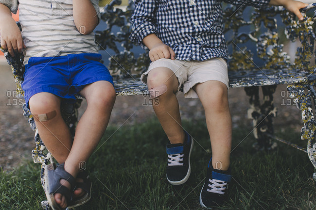 Two little boys with bandages on their knees
