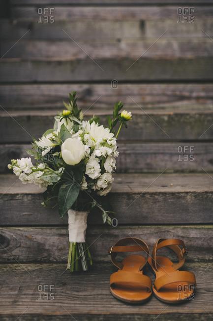 White floral bouquet beside tan sandals