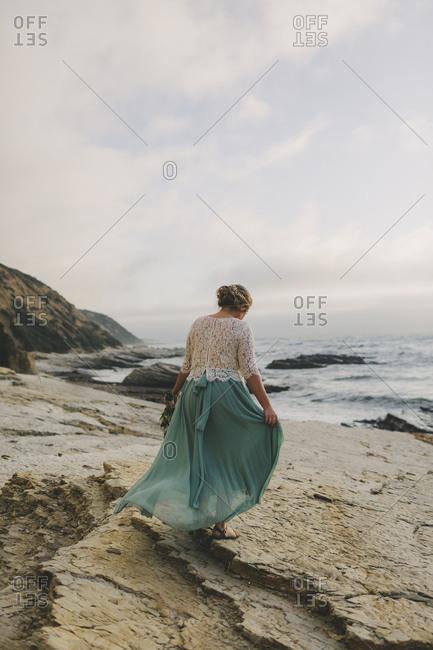 Rear view of bride walking on a beach