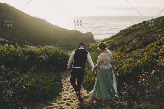 Bride and groom walking down path to the sea