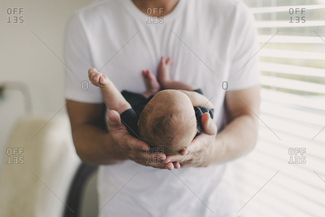 Man holding his newborn baby in the palms of his hands