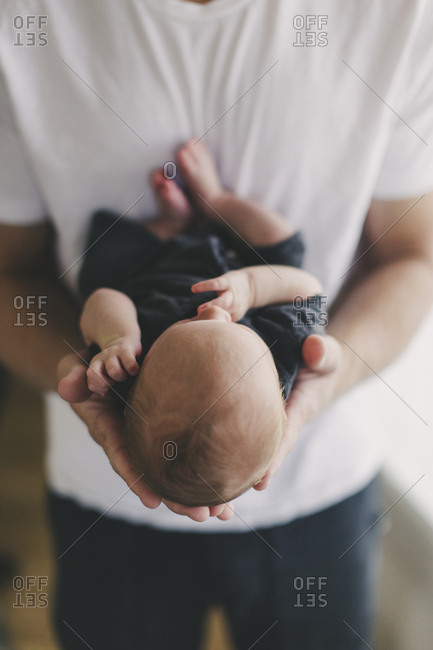 Father holding his newborn baby in the palms of his hands