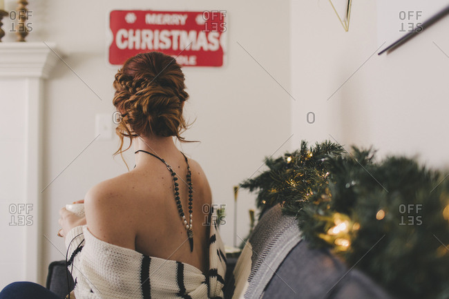 Rear view of redhead woman sitting on sofa drinking coffee at Christmas