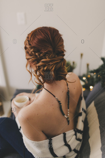 Rear view of redhead woman sitting on sofa drinking coffee
