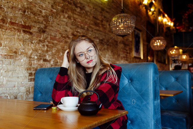 Thoughtful cute blonde girl with glasses sitting and having a cup of tea at the coffee shop