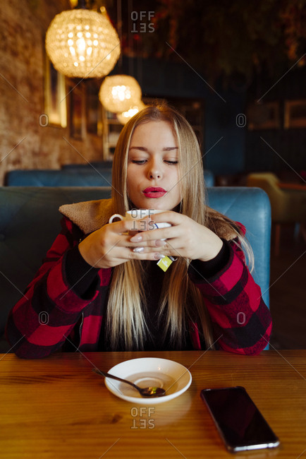 Pretty blonde girl holding a cup of tea at the coffee shop and blowing the tea