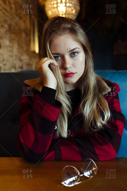 Confident pretty blonde girl sitting on a coffee shop and looking at the camera