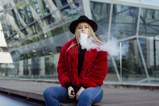 Blonde girl with hat and red jacket smoking with vaper rmachine on the street