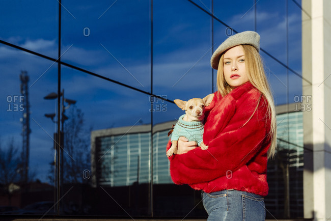 Confident pretty blonde girl carrying a small dog in her arms and looking at the camera in the street