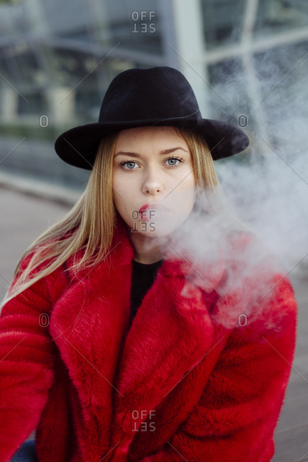 Cute blonde girl with hat and red jacket smoking with vaper rmachine on the street
