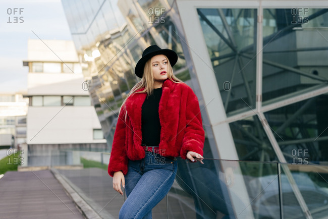 Cute blonde girl with hat and red jacket standing on the street and looking away