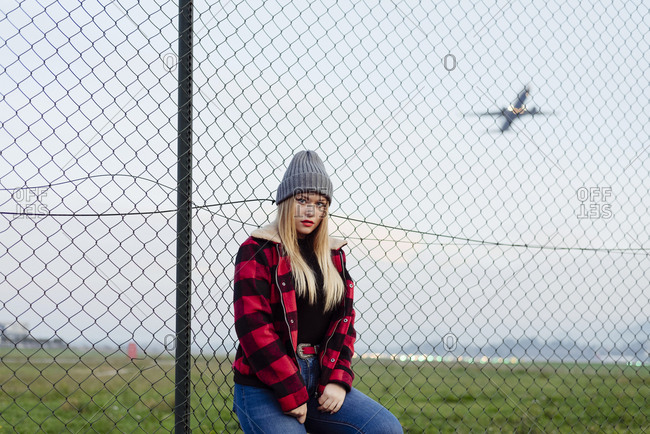 Pretty blonde girl with wool hat leaning on the fence near to the airport and looking at the camera