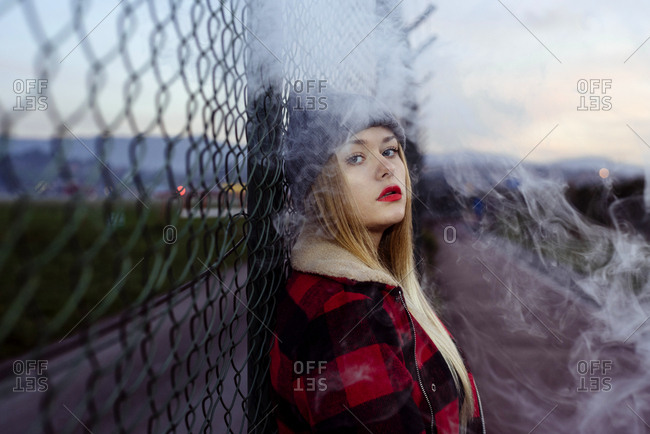 Pretty blonde girl with wool hat leaning on the fence and smoking with vaper machine