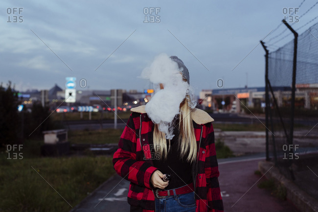 Pretty blonde girl with wool hat standing on the street and smoking with vaper machine
