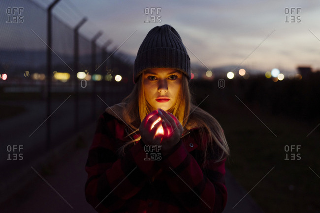Pretty blonde girl with wool hat holding a garland of lights looking at the camera on the street
