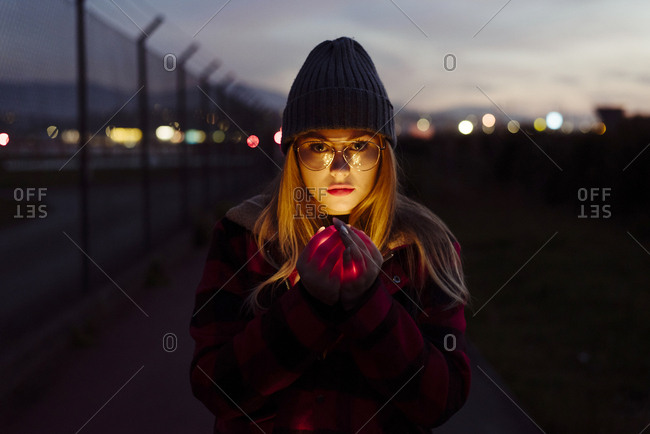 Pretty blonde girl with wool hat and glasses holding a garland of lights looking at the camera on the street