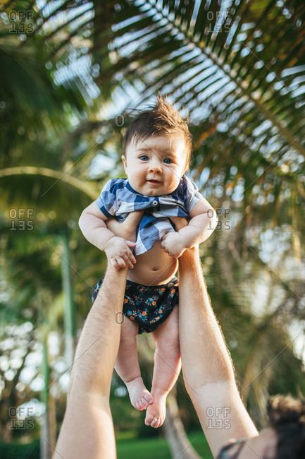 Baby girl being held up overhead in a  tropical setting