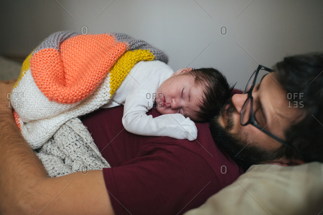 Sleeping newborn on dad's chest covered by blanket