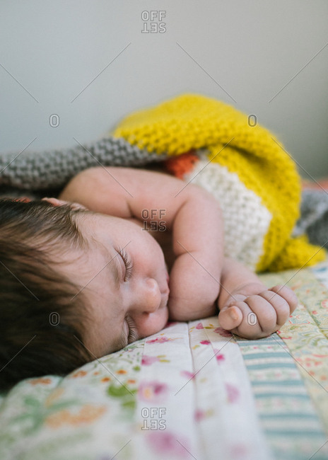 Sleeping newborn on floral quilt