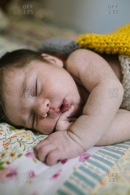 Sleeping newborn on floral quilt with pursed lips