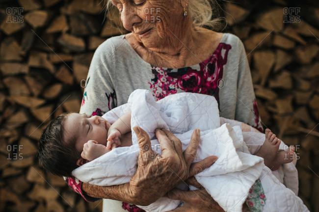 Elderly woman holding newborn baby in white blanket