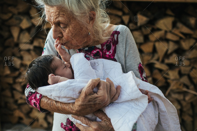 Elderly woman holding and kissing newborn baby's hand