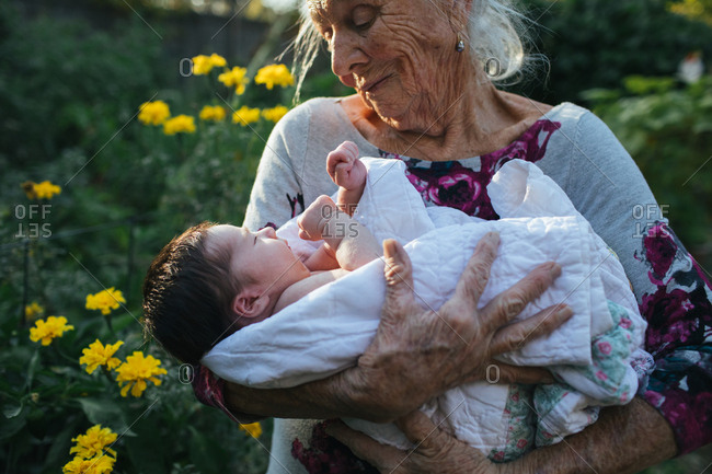 Elderly woman holding newborn in garden
