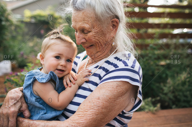 Elderly woman in striped shirt holding baby girl on lap