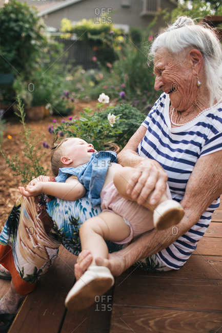 Elderly woman playing with baby girl on lap outside
