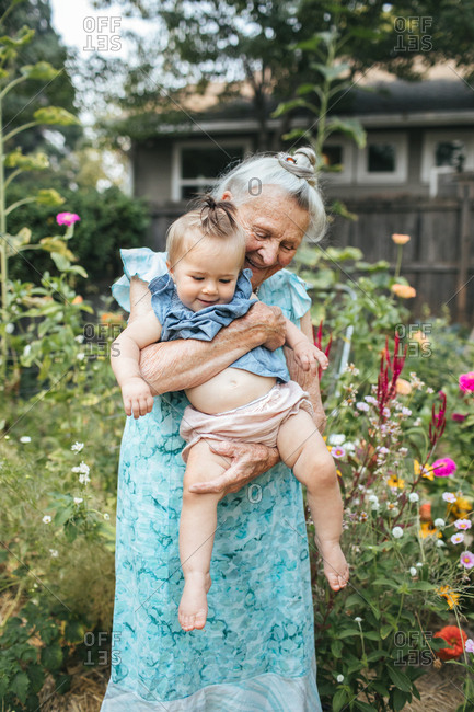 Elderly woman holding smiling baby in flower garden