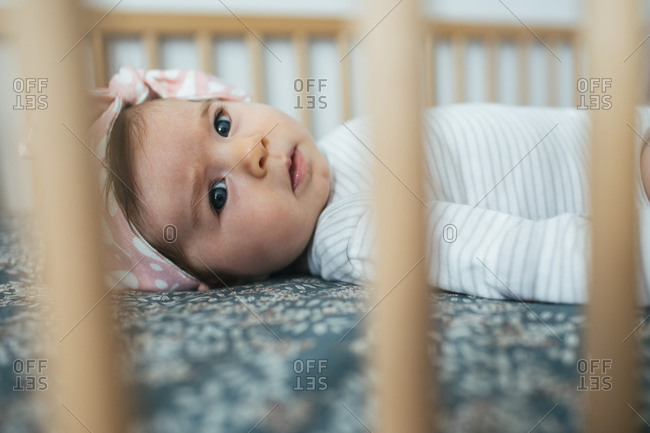 Baby in crib wearing pink headband