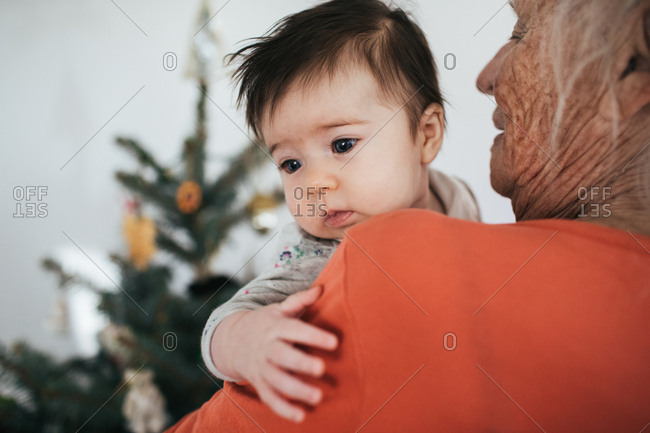 Baby girl held by elderly woman with christmas tree