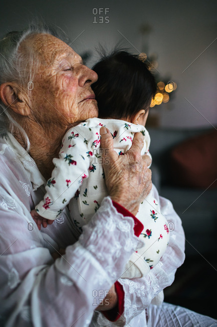 Elderly woman holding dark haired baby with her eyes closed