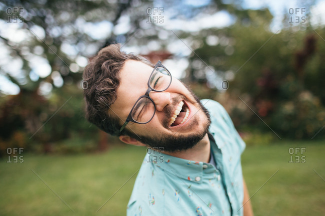 Brunette man with beard and glasses smiling at camera